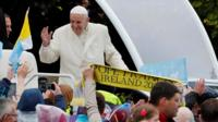Pope Francis waves to the crowd as he travels in the popemobile to the Knock shrine