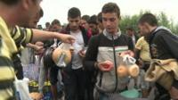 People being given bread rolls and apples
