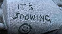"A light dusting of snow on a car with the words ""it's snowing"" written into the snow."