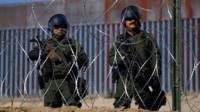 Two men with guns and helmets behind barbed wire fence, security patrol at border