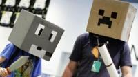 Minecraft fans wearing painted boxes on their heads to resemble Minecraft characters