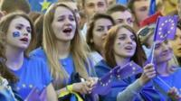 People wave European Union flags during a mass open-air concert on European Square in Kiev on June 10, 2017, dedicated to the abolition of EU visas for Ukrainian citizens