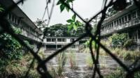 Image of an abandoned building through an old wire fence