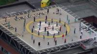 People on a helipad clapping