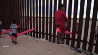 Children play on seesaws on the US border