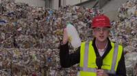 Dan Johnson holding plastic bottle in front of mounds of plastic