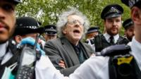 Piers Corbyn surrounded by police officers