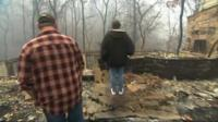 Couple looking at burned out house