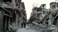 Young Syrian men surrounded by rubble in Homs, file pic from 29 Nov 2012