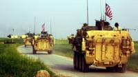 US forces accompanied by YPG fighters drive their armoured vehicles in northern Syria in April 2017