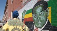 A man stands next to a mural of Robert Mugabe