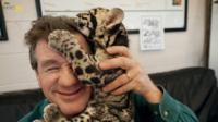 After a photo shoot at the Columbus Zoo in Ohio, a clouded leopard cub climbs on Sartore's head.