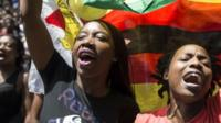 Women holding a flag of Zimbabwe