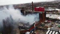 Smoke rises from burnt-out mill