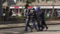 Police drag away protester