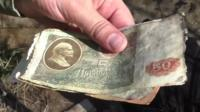 One of the Abandoned Country team holds Soviet-era bank notes