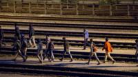 Migrants walk along rail tracks in Calais on 29 July 2015