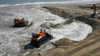 Bulldozers move sand on beach