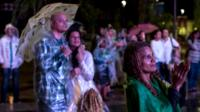 People watch the Rio 2016 Olympics closing ceremony in the rain at the Olympic Boulevard live site
