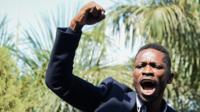 Bobi Wine with his right fist raised in the air
