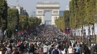 Crowds of pedestrians and cyclists on the Champs-Elysees