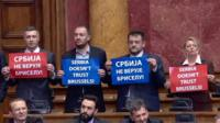 Four Serbian MPs hold signs protesting against the EU