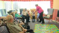 A care home worker talks to residents
