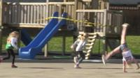 Three children playing outside while remaining distant from each other