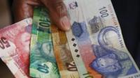 A South African woman holds the South African Rand bank notes in Cape Town