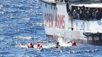 Migrants in water next to Open Arms rescue ship
