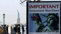 A Shutdown placard is seen at the entrance of the Liberty State ferry terminal as people look on in Battery Park on January 21, 2018 in New York City.