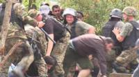 Migrants pushing through police lines