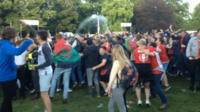 Supporters at the fanzone in Cardiff throw drinks and wave flags in celebration at Wales' second goal in 20 minutes