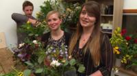 women and men in flower arranging class