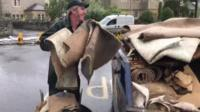 Person throwing a carpet into a skip