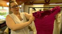 Donated dress inspected by helper