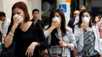"Women cover their faces with masks as haze shrouds Singapore""s central business district."