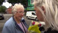 Woman giving a stranger a bouquet of flowers