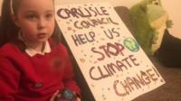 Emily with a sign which says Carlisle council help us stop climate change