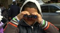 Migrant boy looking through binoculars