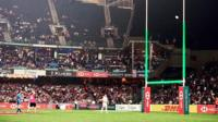 Rugby posts lit green at match