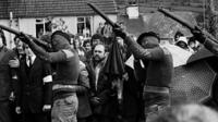Masked IRA members fire a volley of shots at the funeral of hunger striker Raymond McCreesh in 1981