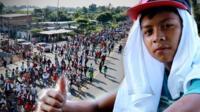 Niño migrante hace una señal positiva con el pulgar con el paso de la caravana en el fondo