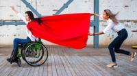 Наталья Камолинкова в инвалидной коляске в образе супергероя
