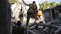 Somali security forces walk at the scene of a blast on October 29, 2017, a day after two car bombs exploded in Mogadishu.