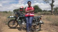 Cecilia Wairimu Ngari standing by her motorbike