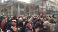 Picture shows protests gathered in a street in Rasht with their arms raised