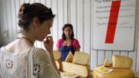 A woman contemplates cheese