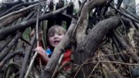 Boy playing in branches