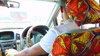 Ugandan man driving car with decorated interior